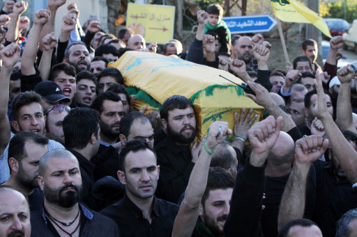Relatives and friends carry the coffin of Hezbollah member Adel Termos, who was killed in Thursday's twin suicide bombings, as they chant slogans during his funeral procession in the southern Lebanese village of Tallousa, Lebanon, Friday, Nov. 13, 2015. Schools and universities across Lebanon are shut as the country mourns the victims of twin suicide bombings that struck a crowded neighborhood south of the capital. (AP Photo/Mohammed Zaatari)