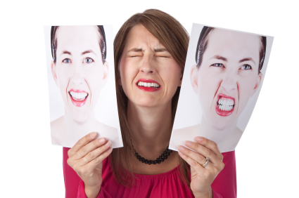 An upset woman holding a photograph of herself happy and angry. She is frustrated with her own mood swings.
