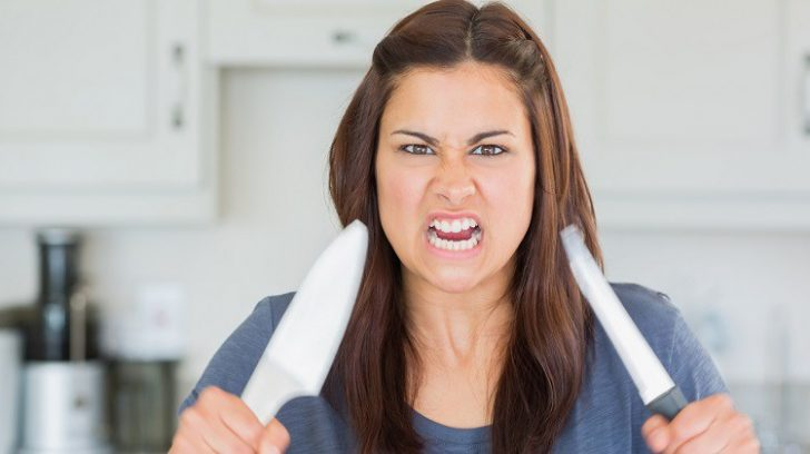 Angry woman holding up knives threateningly
