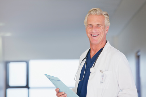 Portrait of smiling doctor holding medical record in hospital corridor