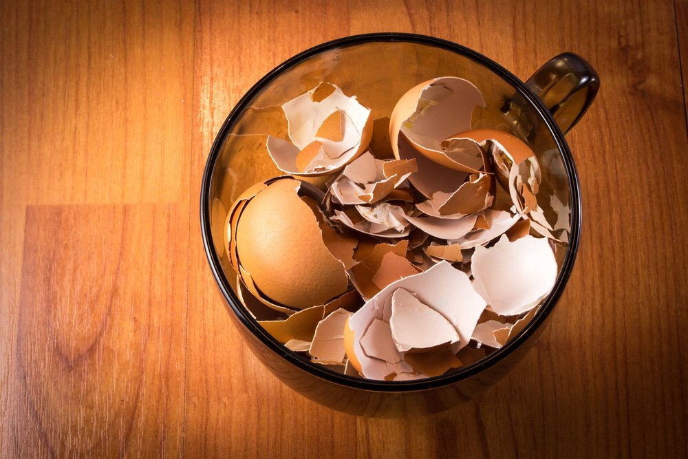 A glass cup of smashed crushed and broken eggshells on natural wood background