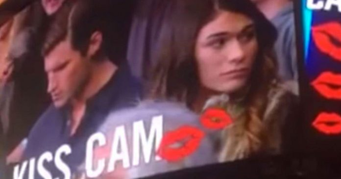 woman kisses man next to her on kiss cam featured