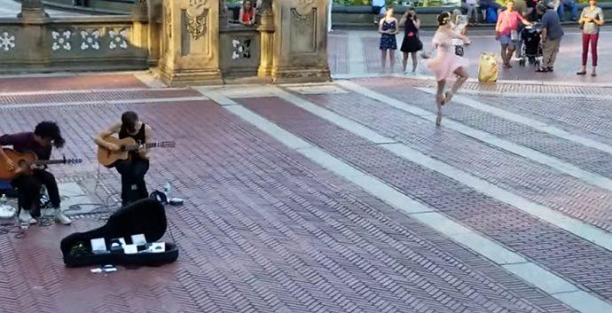 Graban en plena calle a dos músicos callejeros competir con la mujer de rosa para conseguir la atención del público
