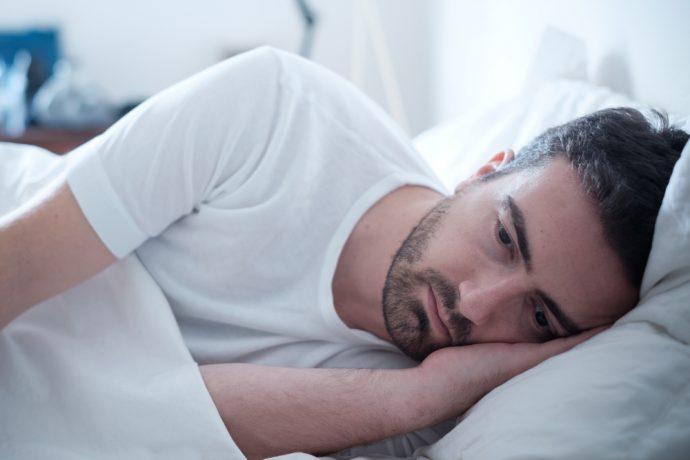 hombre triste cama cansado